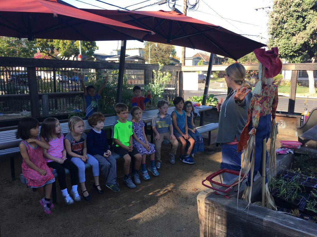 Kindergarteners learn about scarecrows before making their own for auction at the Fall Festival